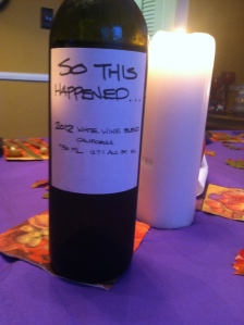 "Bottle of ""So This Happened"" wine with lit candle."