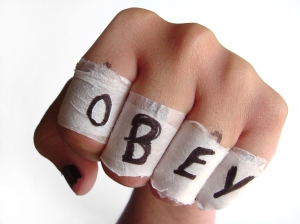 Closed fist with tape around each finger, spelling the word OBEY.