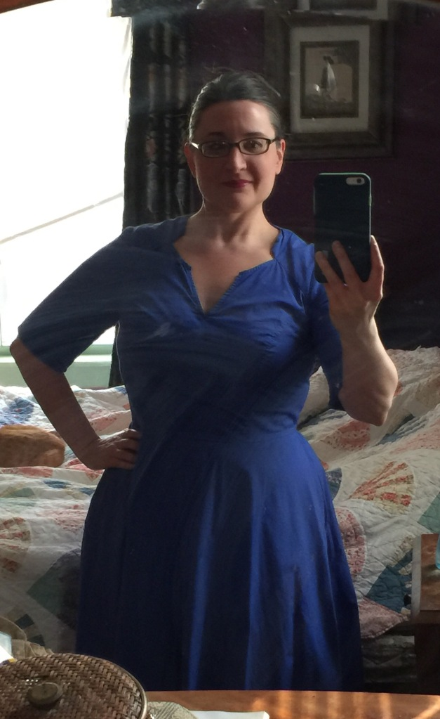 woman wearing a blue dress taking a selfie in the mirror